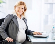 Portrait of pregnant business woman. She is working on a laptop in her office, and looking at camera.   [url=http://www.istockphoto.com/search/lightbox/9786622][img]http://dl.dropbox.com/u/40117171/business.jpg[/img][/url]