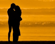 Lovers embracing on the beach at sundown on Morro Strand State Beach